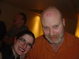 Lisa Lowrance decorates Alan Clarke's forehead while Stephen Jones talks in the background.