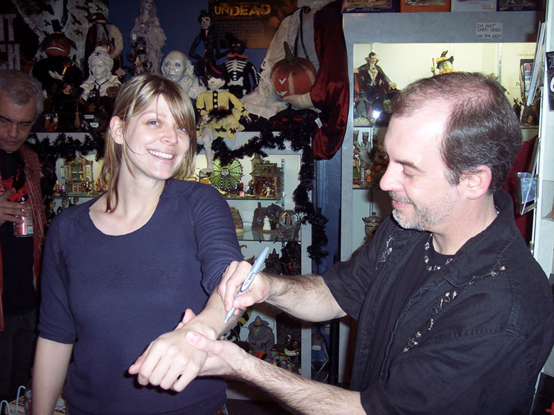 "John Everson ""signs"" Amber Benson's arm at a booksigning in Dark Delicacies in Burbank, CA, 2008."
